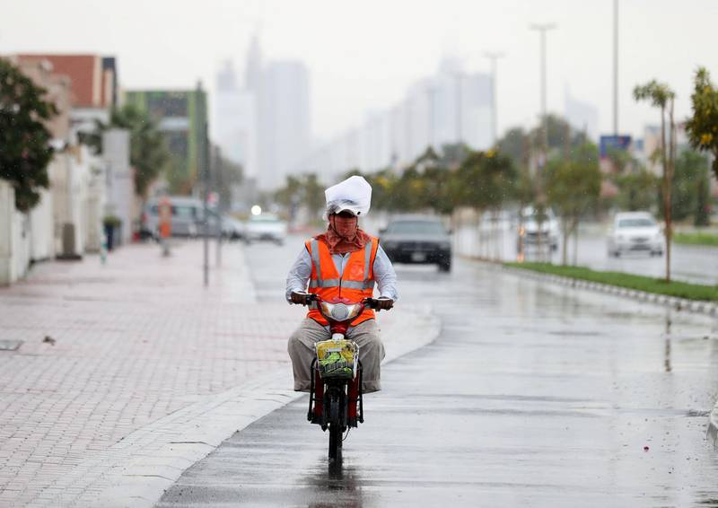Dubai, United Arab Emirates - Reporter: N/A: Weather. A motor cyclist rides covers his face and has a bag on his head to stay dry as the rain comes down in Dubai. Saturday, March 21st, 2020. Jumeirah, Dubai. Chris Whiteoak / The National