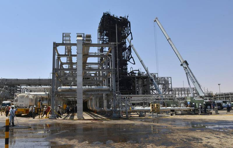 Employes of Aramco oil company stand near a heavily damaged installation in Saudi Arabia's Khurais oil processing plant on September 20, 2019. - Saudi Arabia said on September 17 its oil output will return to normal by the end of September, seeking to soothe rattled energy markets after attacks on two instillations that slashed its production by half. The strikes on Abqaiq –- the world's largest oil processing facility –- and the Khurais oil field in eastern Saudi Arabia roiled energy markets and revived fears of a conflict in the tinderbox Gulf region. (Photo by Fayez Nureldine / AFP)