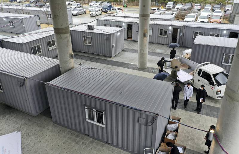 Workers move equipments into containers set up as a makeshift medical facility to accommodate COVID-19 patients at a hospital's grounds in Daegu, South Korea, Friday, Feb. 28, 2020. Japan's schools prepared to close for almost a month and entertainers, topped by K-pop superstars BTS, canceled events as a virus epidemic extended its spread through Asia into Europe and on Friday, into sub-Saharan Africa. (Kim Hyun-tae/Yonhap via AP)
