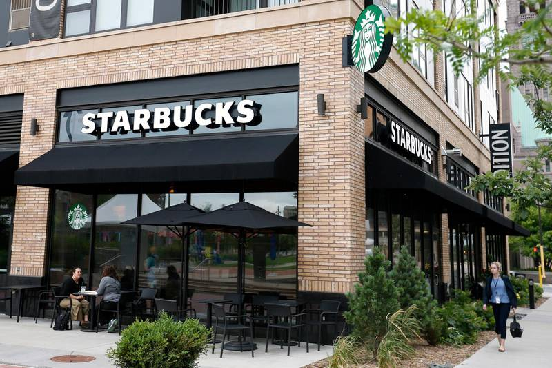 In this July 10, 2019, photo customers visit at a Starbucks in Minneapolis. Starbucks Corp. reports financial earnings on Thursday, July 25, 2019. (AP Photo/Jim Mone)