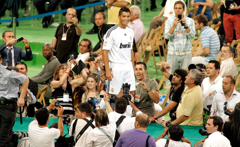 Real Madrid's new player Portuguese Cristiano Ronaldo (C) smiles during his official presentation at the Santiago Bernabeu stadium in Madrid on July 6, 2009. Real acquired the 24-year-old Portuguese striker from Manchester United last month on a six-year deal worth 94 million euros (131 million dollars) and Spanish media reports that he will be paid 13 million euros each season. AFP PHOTO / SALVADOR RODRIGUEZ (Photo by SALVADOR RODRIGUEZ / AFP)