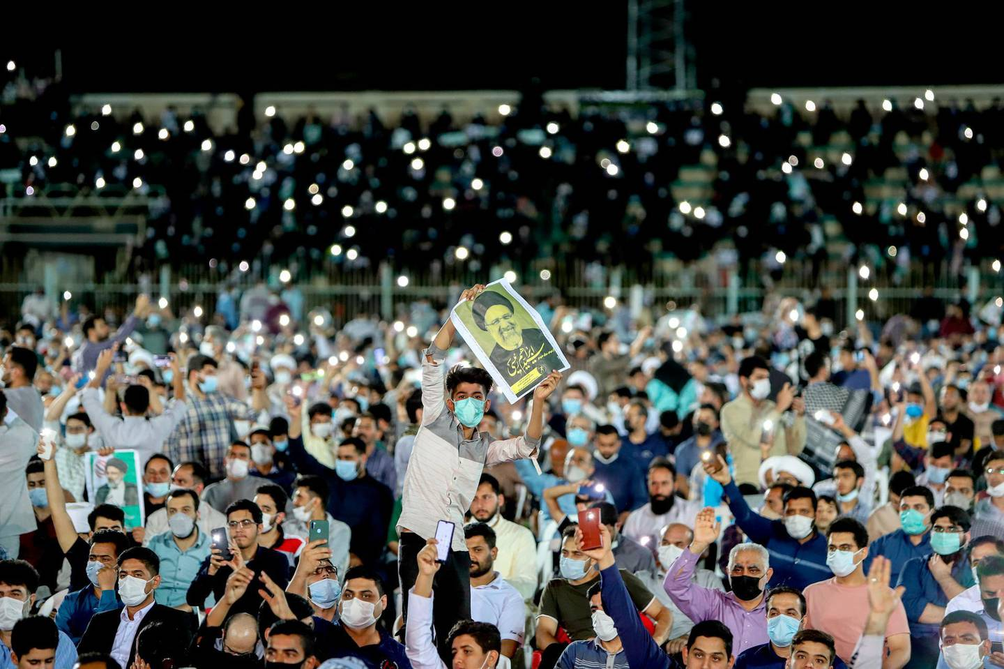 In this Wednesday, June 9, 2021 photo, a supporter of the presidential candidate Ebrahim Raisi, currently judiciary chief, hold his posters during a campaign rally at the Takhti Stadium in Ahvaz, Iran. Around 5,000 of people have gathered in a football stadium in southeastern city of Ahvaz to support the Iranian hard-line presidential candidate, Iranian media reported. (Alireza Mohammadi/ISNA via AP)