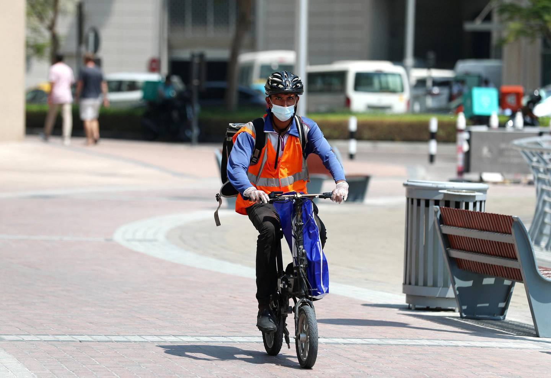 Dubai, United Arab Emirates - N/A. News. Coronavirus/Covid-19. A man makes his deliveries on a moped in the marina. Friday, September 11th, 2020. Dubai. Chris Whiteoak / The National