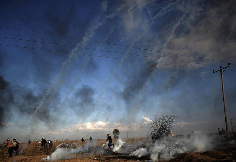 epa06392202 Palestinian protesters run for cover during clashes near the border with Israel, against US President decision to recognize Jerusalem as the capital of Israel, in the east of Gaza City, 15 December 2017. Two Palestinians were killed during the clashes in the east of Gaza Strip. US president Donald J. Trump on 06 December announced he is recognizing Jerusalem as the Israel capital and will relocate the US embassy from Tel Aviv to Jerusalem.  EPA/MOHAMMED SABER