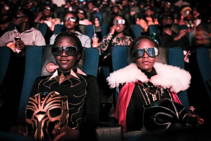 """Cosplayers watches the film """"Black Panther"""" in 3D which featuring Oscar-winning Mexico born Kenyan actress Lupita Nyong'o during Movie Jabber's Black Panther Cosplay Screening in Nairobi, Kenya, on February 14, 2018. Black Panther is a Superhero film based on the Marvel Comics character featured the first black superhero as Black Panther in advanced fictional African nation. Nyong'o who won the Academy Award for best supporting actress in 12 Years a Slave in 2014, plays a major role as a female warrior in the film.  / AFP PHOTO / Yasuyoshi CHIBA"""