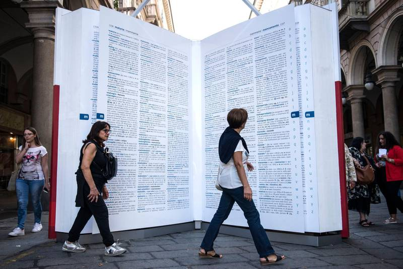 TURIN, ITALY - OCTOBER 02, 2019: People stand infront of a giant dictionary installed as an initiative by publishing house Zanichelli to save the unused words in the Italian language, on October 02, 2019 in Turin, italy. (Photo by Stefano Guidi/Getty Images)