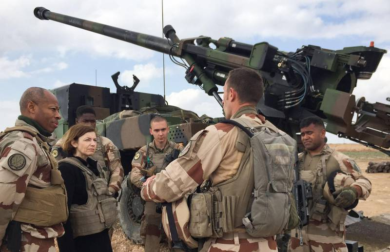 """(FILES) In this file photo taken on February 9, 2019 French General Jean-Marc Vigilant (L) and French Defence Minister Florence Parly (2nd L) talk to French soldiers engaged in the """"Operation Chammal"""", the French military operation within """"Operation Inherent Resolve"""", the international coalition against the Islamic State (IS) group, as they stand in front of a wheeled 155 mm gun-howitzer CAESAR system (truck equipped with an artillery system), near Al-Qaim, a few kilometres away from the last scrap of territory held by IS in eastern Syria. France will withdraw its contingent of troops from Iraq, mostly trainers to local armed forces, because of the coronavirus pandemic, the chief of staff said on March 25, 2020. France has around 200 military personnel working in Iraq either as trainers or in the headquarters of coalition forces in Baghdad.   / AFP / Daphné BENOIT"""