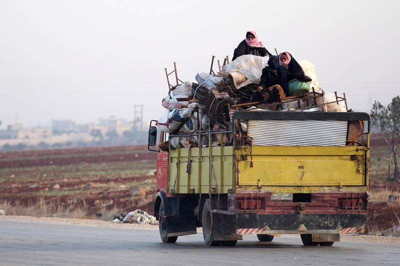 A displaced family from a village in southern Idlib head on the Damascus-Aleppo motorway towards the northern part of the rebel-held province on December 29, 2017.  Clashes pitting mainly jihadist and rebel fighters against regime forces backed by Russian warplanes killed at 66 people on the edge of Syria's northwestern Idlib province, a monitor said. / AFP PHOTO / OMAR HAJ KADOUR