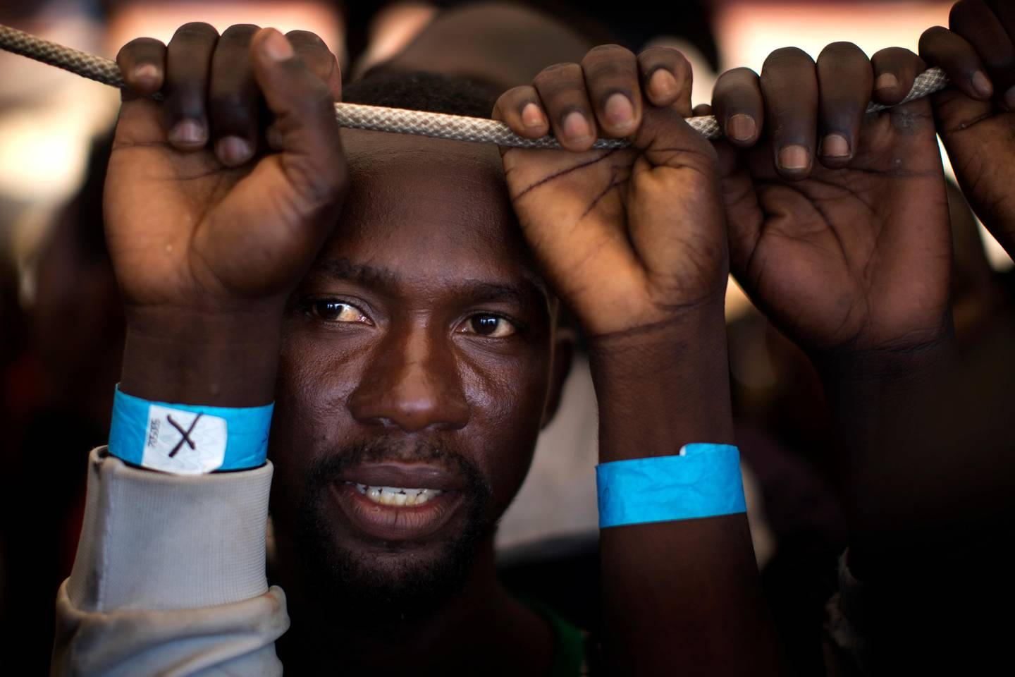 FILE - In this June 17, 2017 file photo, Samuel, 25, from Nigeria, waits his turn to leave the Golfo Azzurro rescue vessel, after being rescued from a packed boat from Libya, by members of Proactive Open Arms, as they arrive at the port of Pozzallo, south of Sicily, Italy. Under a deal backed by Italy, Libya��������s struggling government in Tripoli has paid militias that were once involved in smuggling migrants to now prevent migrants from crossing the Mediterranean to Europe, one reason for a dramatic drop in the traffic, according to militia and security officials. (AP Photo/Emilio Morenatti, File)
