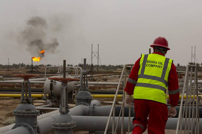 An employee watches the burning of excess hydrocarbons at the Nahr Bin Omar natural gas field, north of the southern Iraqi port of Basra on April 21, 2020.  / AFP / Hussein FALEH