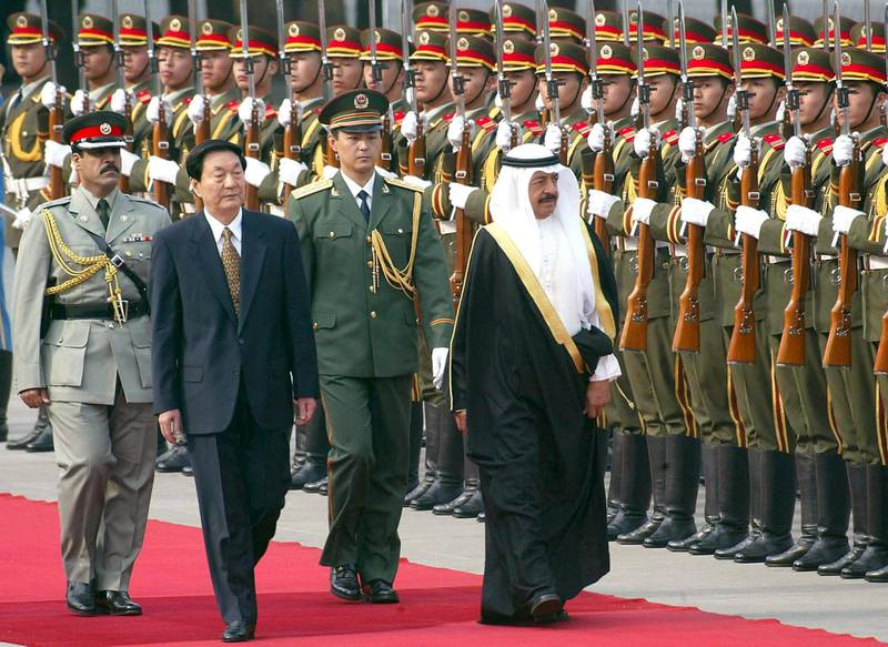 Chinese Premier Zhu Rongji  accompanies Bahrain's Prime Minister Khalifa bin Salman Al-Khalifa, as they review a guard-of-honour during a welcoming ceremony on Tiananmen Square, outside the Great Hall of the People in Beijing, 16 May 2002.   The Gulf kingdom of Bahrain is seeking to promote economic ties with China, as it embarked on democratic reform and held its first municipal elections since 1957, while is increasingly looking East.             AFP PHOTO/GOH Chai Hin (Photo by AFP)