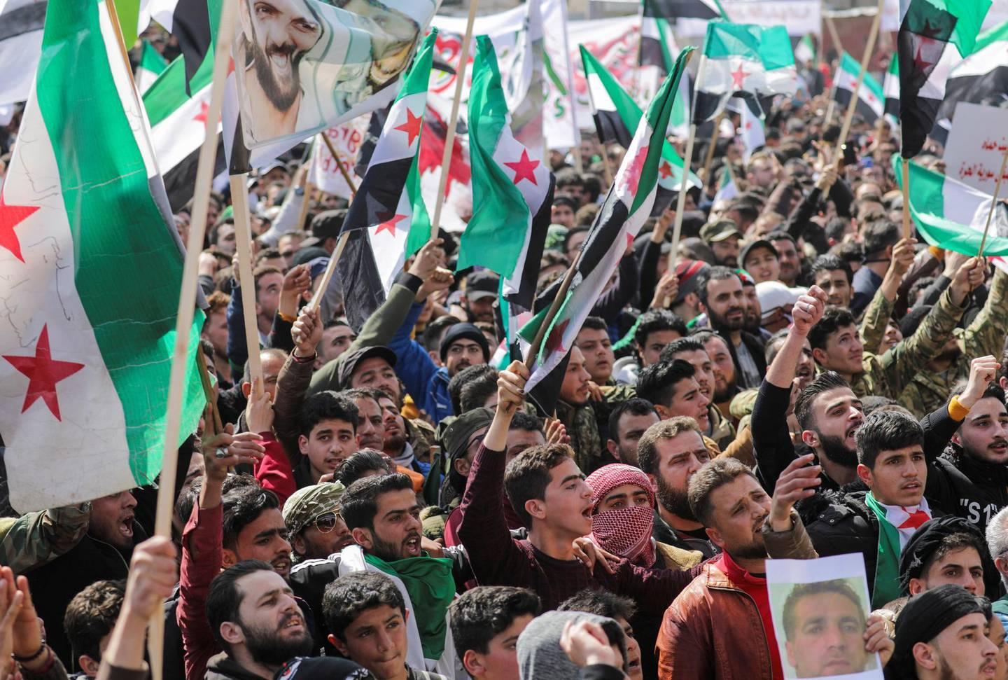 People carry banners and opposition flags during a demonstration, marking the 10th anniversary of the start of the Syrian conflict, in the opposition-held Idlib, Syria March 15, 2021. REUTERS/Khalil Ashawi