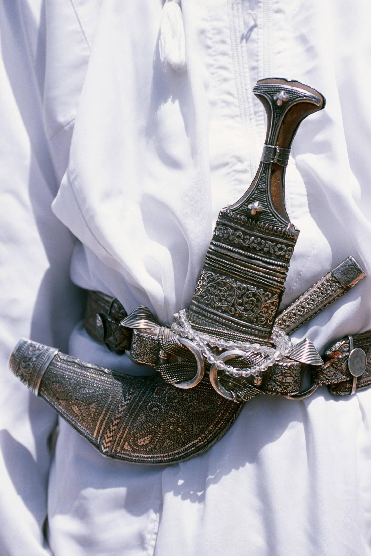 Oman, Jabal al Akhdar, Jebel Shams. Omani men wear the traditional long white robes and ceremonial khanjar or curved dagger up on Al Jabal al Akhdar. Getty Images