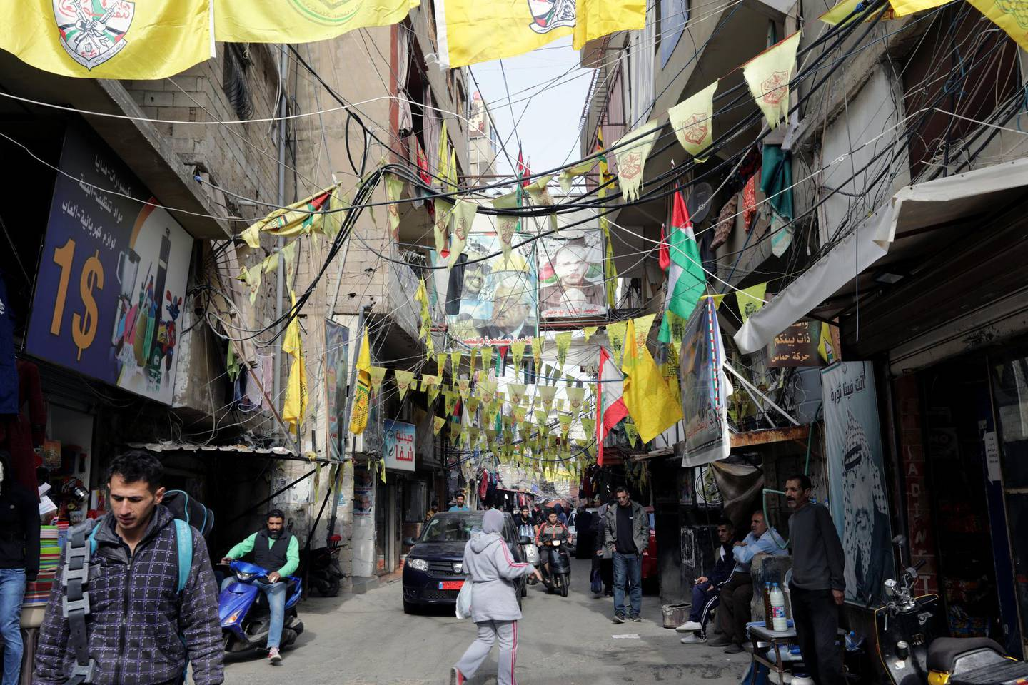 """A picture taken on December 21, 2017 shows a view of posters showing Palestinian leaders and Fatah flags hanging in a street in the Burj al-Barajneh camp, a southern suburb of the Lebanese capital Beirut. - More than 174,000 Palestinian refugees live in Lebanon, authorities announced on December 21, in the first-ever census of its kind for a country where demographics have long been a sensitive subject. The census was carried out by the government's Lebanese-Palestinian Dialogue Committee in 12 Palestinian camps as well as 156 informal """"gatherings"""" across the country. (Photo by ANWAR AMRO / AFP)"""