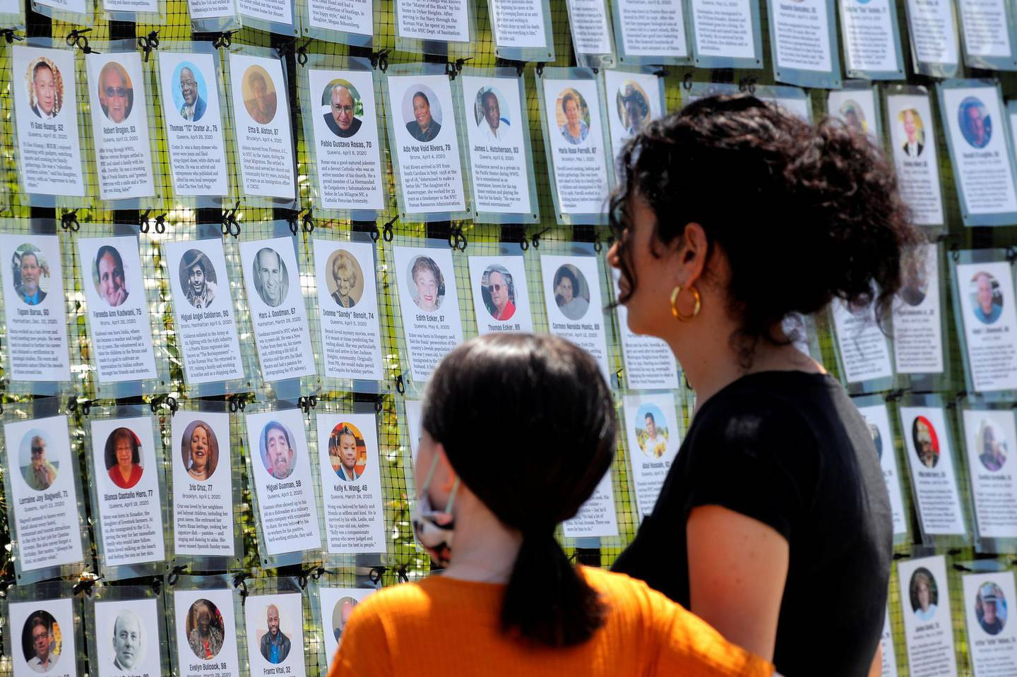 """A woman and child look at the """"Naming the Lost Memorials,"""" as the U.S. deaths from the coronavirus disease (COVID-19) are expected to surpass 600,000, at The Green-Wood Cemetery in Brooklyn, New York, U.S., June 10, 2021. REUTERS/Brendan McDermid"""