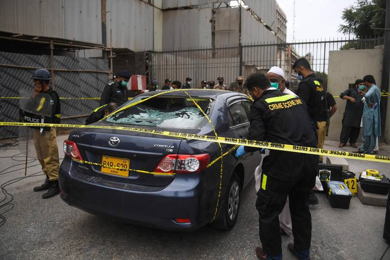 TOPSHOT - Policemen guard as members of Crime Scene Unit investigate around a car used by alleged gunmen at the main entrance of the Pakistan Stock Exchange building in Karachi on June 29, 2020. Gunmen attacked the Pakistan Stock Exchange in Karachi on June 29, with four of the assailants killed, police said. / AFP / Asif HASSAN