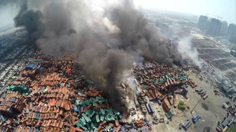 This screen grab taken from AFPTV shows an aerial image taken on August 13, 2015 of smoke rising from debris the day after a series of explosions hit a chemical warehouse in the city of Tianjin, in northern China.  A Chinese military team of nuclear and chemical experts began work on August 14 at the site of two massive explosions in the city of Tianjin, state media said, as pressure grows for authorities to explain the cause of blasts that left 50 dead. CHINA OUT     AFP PHOTO / AFPTV (Photo by AFPTV / AFPTV / AFP)