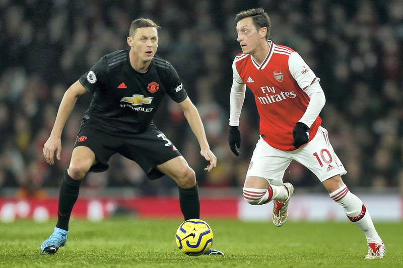 Arsenal's German midfielder Mesut Ozil (R) vies with Manchester United's Serbian midfielder Nemanja Matic (L) during the English Premier League football match between Arsenal and Manchester United at the Emirates Stadium in London on January 1, 2020. (Photo by Ian KINGTON / IKIMAGES / AFP) / RESTRICTED TO EDITORIAL USE. No use with unauthorized audio, video, data, fixture lists, club/league logos or 'live' services. Online in-match use limited to 45 images, no video emulation. No use in betting, games or single club/league/player publications.