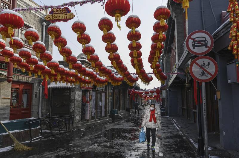 BEIJING, CHINA - FEBRUARY 07: A Chinese woman wears a protective mask as she walks in a nearly empty and shuttered commercial street on February 7, 2020 in Beijing, China. The number of cases of a deadly new coronavirus rose to more than 31000 in mainland China Friday, days after the World Health Organization (WHO) declared the outbreak a global public health emergency. China continued to lock down the city of Wuhan in an effort to contain the spread of the pneumonia-like disease which medical experts have confirmed can be passed from human to human. In an unprecedented move, Chinese authorities have put travel restrictions on the city which is the epicentre of the virus and municipalities in other parts of the country affecting tens of millions of people. The number of those who have died from the virus in China climbed to over 636 on Friday, mostly in Hubei province, and cases have been reported in other countries including the United States, Canada, Australia, Japan, South Korea, India, the United Kingdom, Germany, France and several others. The World Health Organization has warned all governments to be on alert and screening has been stepped up at airports around the world. Some countries, including the United States, have put restrictions on Chinese travellers entering and advised their citizens against travel to China. (Photo by Kevin Frayer/Getty Images)