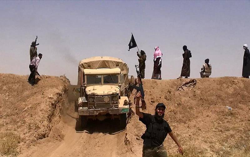 """An image made available by the jihadist Twitter account Al-Baraka news on June 11, 2014 allegedly shows militants of the jihadist group Islamic State of Iraq and the Levant (ISIL) waving the Islamic Jihad flag and holding up their weapons as a vehicle drives on a newly cut road through the Syrian-Iraqi border between the Iraqi Nineveh province and the Syrian town of Al-Hasakah. AFP PHOTO / HO / ALBARAKA NEWS === RESTRICTED TO EDITORIAL USE - MANDATORY CREDIT """"AFP PHOTO / HO / ALBARAKA NEWS"""" - NO MARKETING NO ADVERTISING CAMPAIGNS - DISTRIBUTED AS A SERVICE TO CLIENTS === (Photo by - / ALBARAKA NEWS / AFP)"""