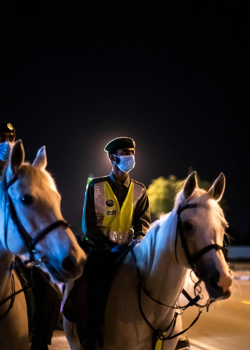DUBAI, UNITED ARAB EMIRATES. 16 APRIL 2020. Dubai Mounted Police officers, in Al Aweer, patrol residential and commercial areas to insure residents are staying safe indoors during COVID-19 lockdown. They patrol the streets from 6PM to 6AM.The officers of the Dubai Mounted Police unit have been playing a multifaceted role in the emirate for over four decades. The department was established in 1976 with seven horses, five riders and four horse groomers. Today it has more than 130 Arabian and Anglo-Arabian horses, 75 riders and 45 groomers.All of the horses are former racehorses who went through a rigorous three-month-training programme before joining the police force. Currently, the department has two stables – one in Al Aweer, that houses at least 100 horses, and the other in Al Qusais, that houses 30 horses.(Photo: Reem Mohammed/The National)Reporter:Section: