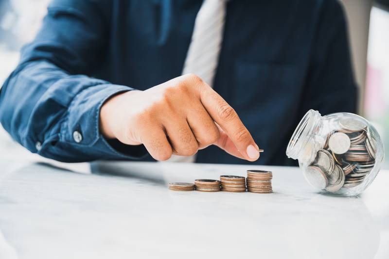 Close up businessman holding putting money coin stack with coin in glass. Investment concept, Saving money concept, Finance money concept