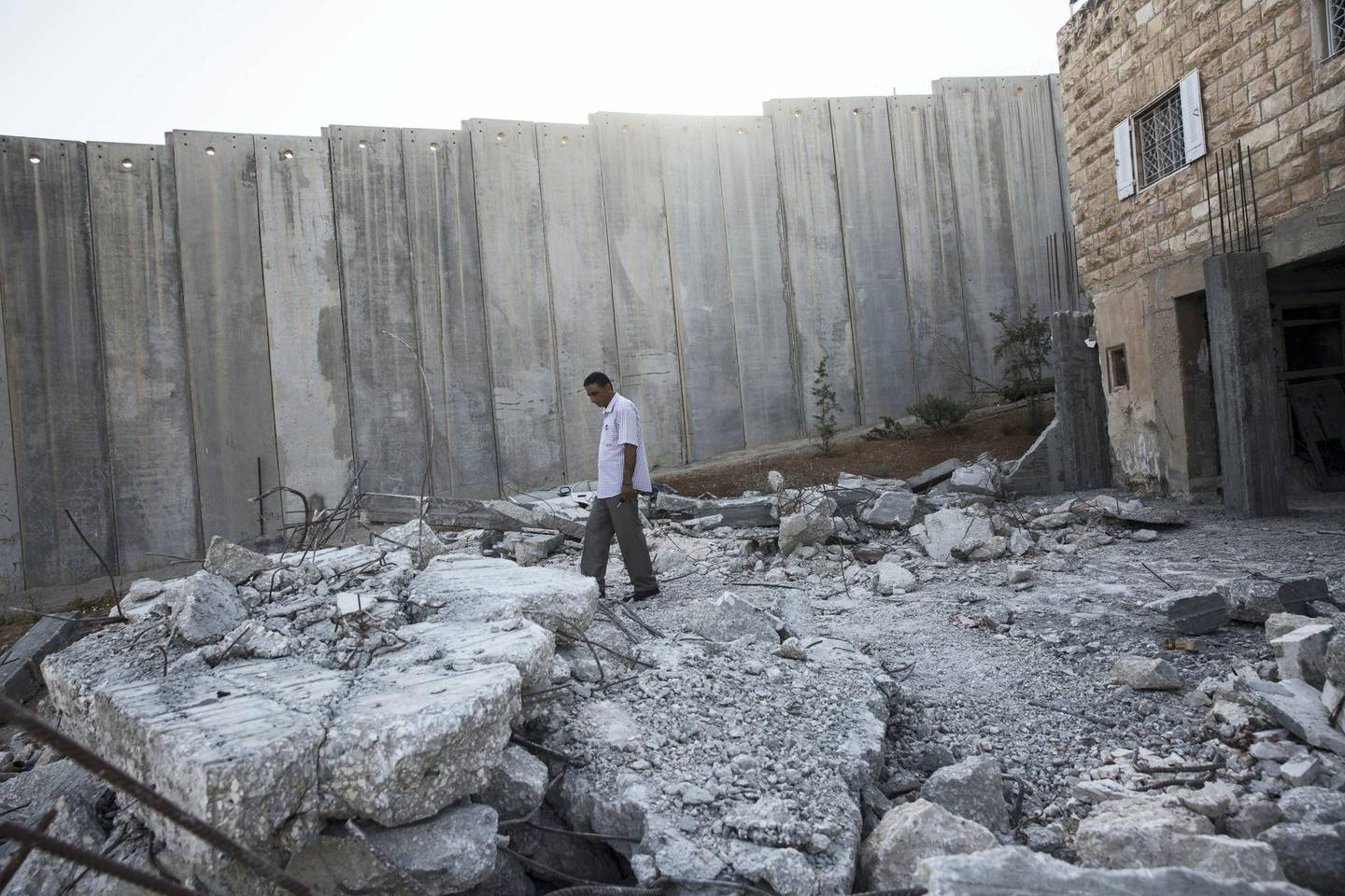 Musa Wohish,49, walks in the rubble of the home his brother tried to build next to his grandfather's home in the divided West Bank village of Abu Dis on September 2,2018. Musa has not been able to travel to Jerusalem since he was a child even though he can see the Al Aqsa Mosque from high points that overlook Israel's  8 meter high separation wall that now divides the village. He has been unemployed for over 15 years . His family has lived in Abu Dis since 1937.(Photo by Heidi Levine for The National ).