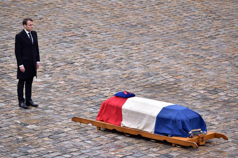 epaselect epa06634003 French President Emmanuel Macron stands in front of the flag-draped coffin of the Gendarme Lieutenant-Colonel  Arnaud Beltrame during a solemn funeral ceremony, in the courtyard of the Invalides in Paris, France, 28 March 2018. Beltrame was killed after swapping himself in exchange of a female hostage during a terrorist attack in Trebes, southern France, on 23 March 2018.  EPA/CHRISTOPHE PETIT TESSON  EPA-EFE/CHRISTOPHE PETIT TESSON