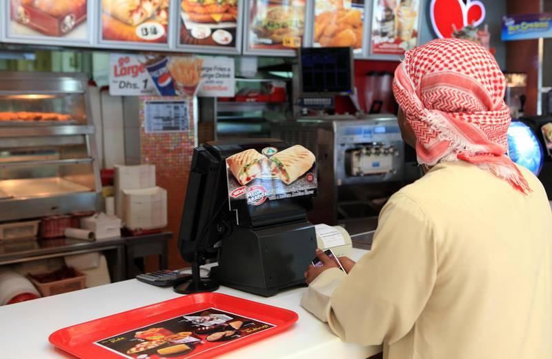 ABU DHABI - 30DEC2010 - A customer waits at KFC counter on Sheikh Rashid bin Maktoum street in Abu Dhabi. Ravindranath K / The National