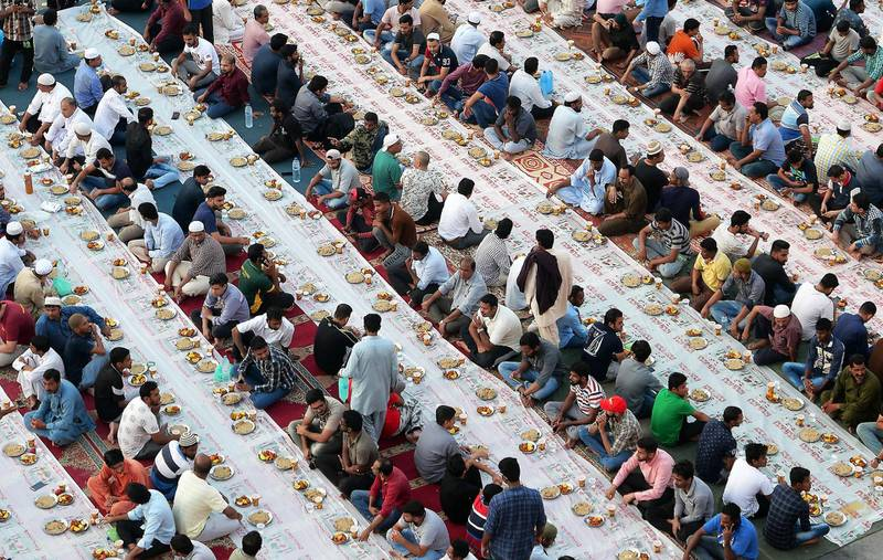 DUBAI,  UNITED ARAB EMIRATES , May 8 – 2019 :-  People sitting together to break their fast during the Ramadan in the parking area near the Al Ghubaiba bus station in Bur Dubai in Dubai. Every year this kind of free Iftar organised by local shop owners and businessmen near the Al Ghubaiba bus station in Dubai. As a photographer I have covered my first Iftar at the same area in 2007. ( Pawan Singh / The National ) For News/Standalone/Big Picture/Online/Instagram