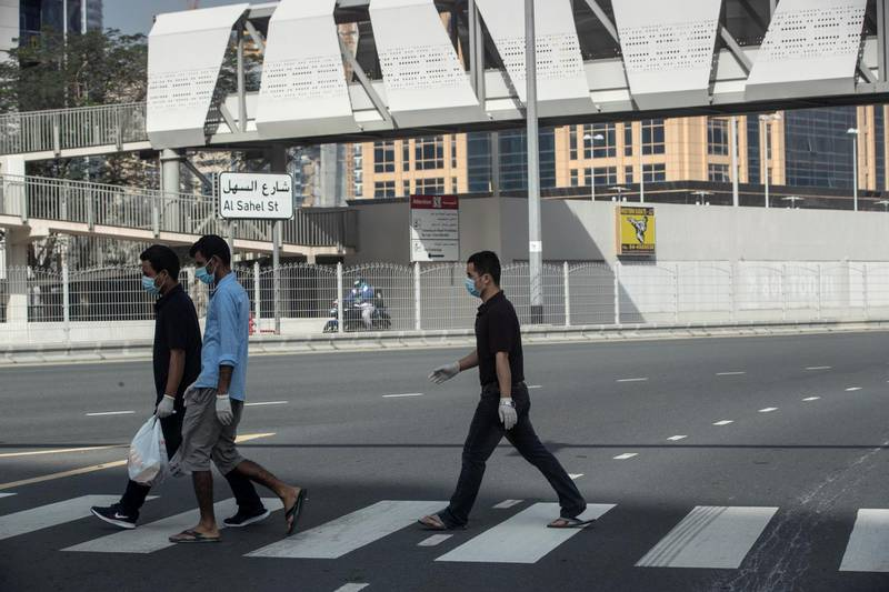 DUBAI, UNITED ARAB EMIRATES. 08 APRIL 2020. Three men wearing face masks and gloves as per Government order walk across a street in Jumeirah Lake Towers. (Photo: Antonie Robertson/The National) Journalist: Standalone. Section: National.