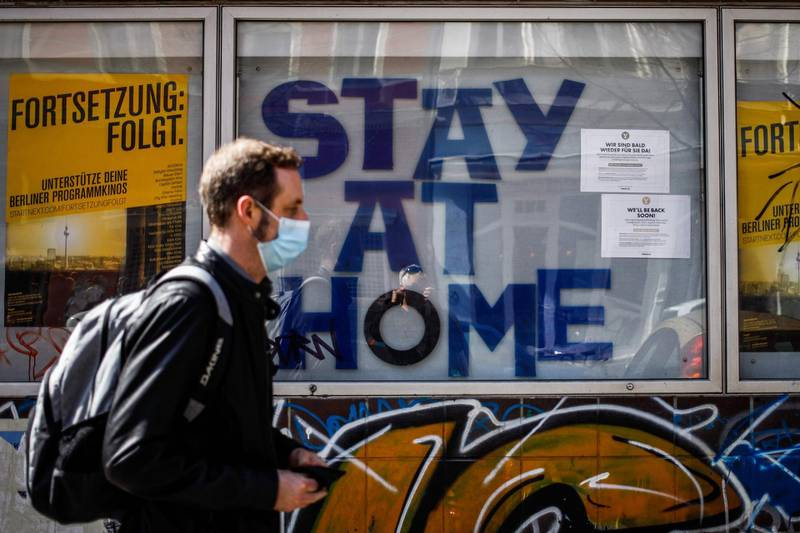 """A man wearing a protective face mask walks past a cinema with the words """"Stay at Home"""" on display in Berlin's Kreuzberg district on April 11, 2020 amid the novel coronavirus COVID-19 pandemic.  / AFP / David GANNON"""