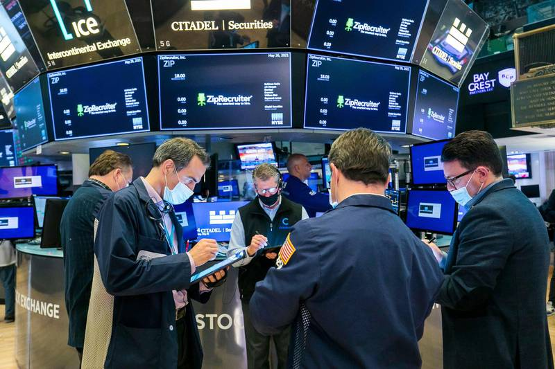 In this photo provided by the New York Stock Exchange, traders gather at a post on the floor, Wednesday, May 26, 2021, in New York. U.S. stocks edged higher in morning trading Wednesday as investors continue to monitor the economic recovery and rising inflation. (Courtney Crow/New York Stock Exchange via AP)