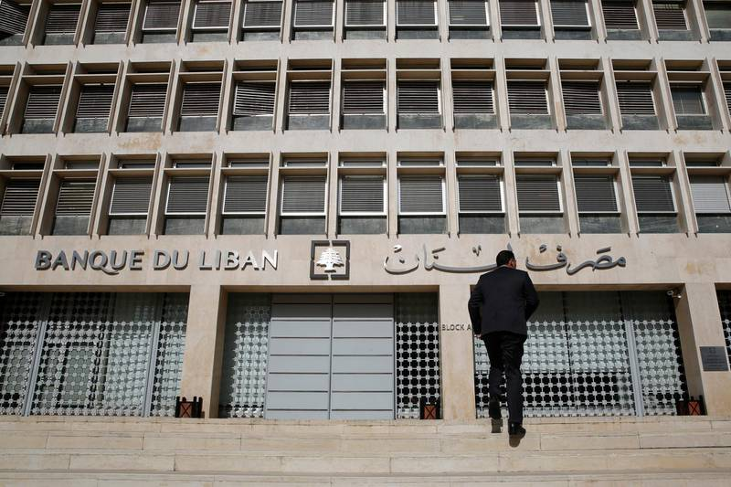 FILE - This Jan. 22, 2019, file photo, a man heads to the Lebanese central bank in Beirut, Lebanon. Lebanon's central bank has issued guarantees to secure U.S. dollars for local banks at the fixed official rate that would cover imports of fuel, wheat and medicine. The central bank's move on Tuesday, Oct. 1, 2019 aims to ease the demand for dollars at a time when many Lebanese are rushing to exchange shops to convert their local currency into dollars. (AP Photo/Hussein Malla, File)