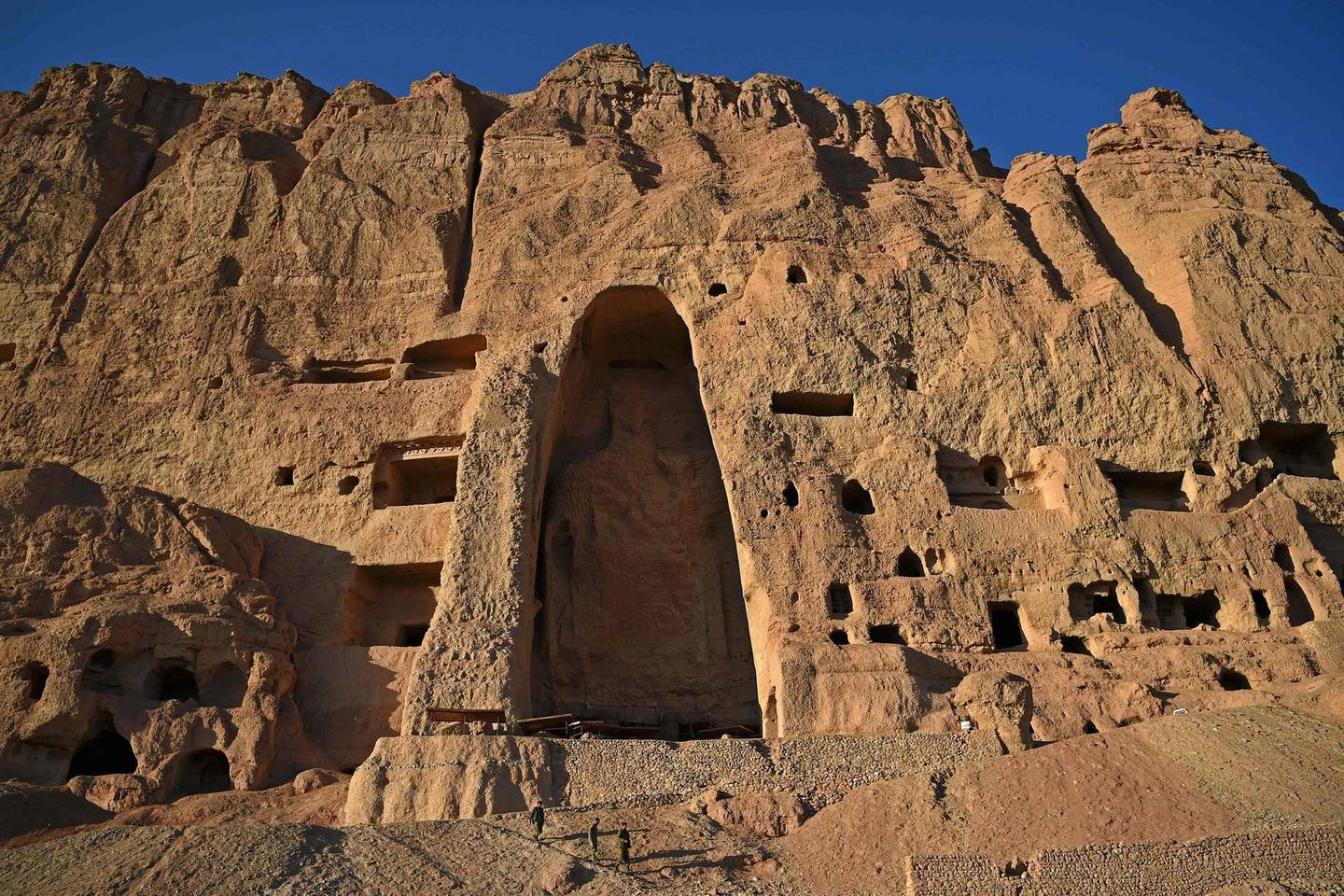 In this picture taken on March 4, 2021, visitors walk at the site of the Buddhas of Bamiyan statues, which were destroyed by the Taliban in 2001, in Bamiyan province. Afghanistan's giant Buddhas stood watch over the picturesque Bamiyan valley for centuries, surviving Mongol invasions and the harsh environment until the Taliban arrived with an apocalyptic worldview that did not care about one of the great wonders of antiquity. - TO GO WITH FOCUS 'AFGHANISTAN-RELIGION-HISTORY-TALIBAN-BUDDHA-STATUES' by USMAN SHARIFI  / AFP / WAKIL KOHSAR / TO GO WITH FOCUS 'AFGHANISTAN-RELIGION-HISTORY-TALIBAN-BUDDHA-STATUES' by USMAN SHARIFI