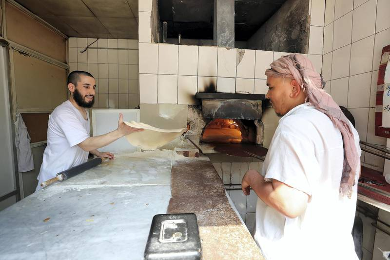 ABU DHABI , UNITED ARAB EMIRATES, September 9 – 2018 :- Zanudin ( left ) making bread at the Shalqar Bakery which is at one of the old building in the Tourist Club area in Abu Dhabi. ( Pawan Singh / The National )  For News. Story by Anna/ John