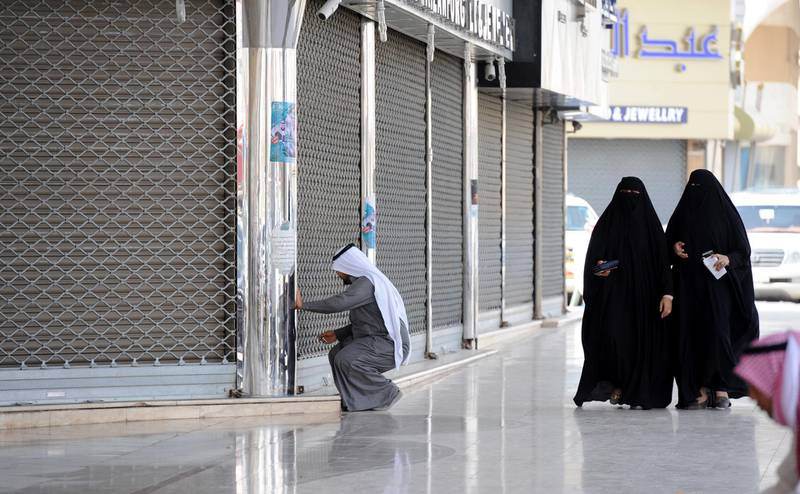 Saudi women walk past a jeweller arriving to open his shop in the Tiba gold market in the capital Riyadh on February 27, 2018. - The Riyadh gold souk is short of salesmen after a government edict to replace foreign workers with Saudis as part of contentious efforts to tackle high unemployment, with many of them who have been long accustomed to a generous cradle-to-grave welfare system regard such jobs as degrading. (Photo by Fayez Nureldine / AFP)