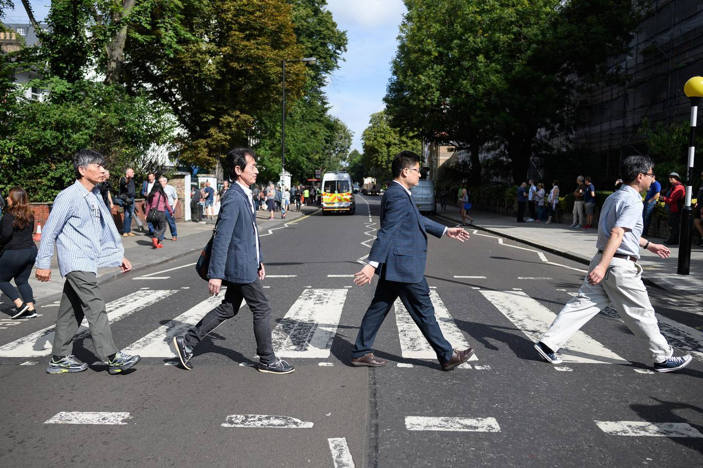 """LONDON, ENGLAND - AUGUST 08: Members of the public recreate the iconic album cover for the Beatles album """"Abbey Road"""" on the same pedestrian crossing, fifty years since it was taken, on August 08, 2019 in London, England. The zebra crossing is just outside the recording studios and has become a popular location for music fans visiting London.  (Photo by Leon Neal/Getty Images)"""