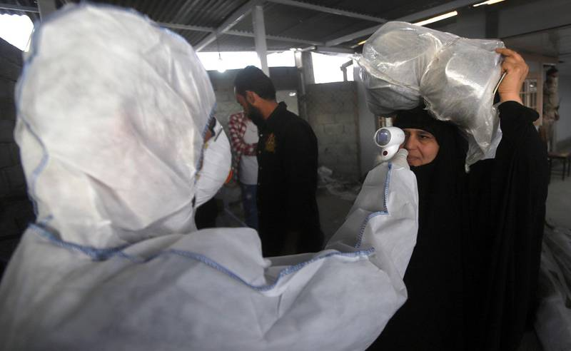 epa08231820 A member of medical team checks the body temperature of an Iraqi woman upon her arrival at Shalamcheh border crossing with Iran, east of Basra city, 500 km southern Iraq on 20 February 2020. Iraqi authorites have taken action to screen those arriving at the airports and border crossings with Iran, while the Iraqi airlines canceled all flights to Iran, following the cases of the deadly Covid-19 Coronavirus diagnosed in iran.  EPA/HAIDER AL-ASSADEE