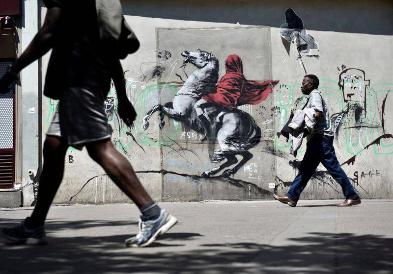 epa06841358 People walk by a recent artwork believed to be attributed to Banksy showing Napoleon rearing his horse, wrapped in a red cloak in the 19th district of Paris, France, 26 June 2018. Several artworks attributed to the anonymous British street artist appeared in the French capital over the last few days.  EPA-EFE/JULIEN DE ROSA