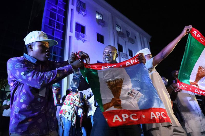 Supporters of the ruling All Progressives Congress (APC) celebrate with party flags in Abuja, Nigeria, after candidate President Mohammadu Buhari was re-elected on February 26, 2019.  Muhammadu Buhari was re-elected Nigeria's president, results showed February 26, 2019, after a delayed poll that angered voters and led to claims of rigging and collusion. Buhari, 76, took an unassailable lead of more than four million votes as the last states were yet to be declared, making it impossible for his nearest rival, Atiku Abubakar, to win. The win was confirmed as Abubakar won in the very last state to declare -- Rivers in the south -- but could not claw back the deficit.  / AFP / KOLA SULAIMON
