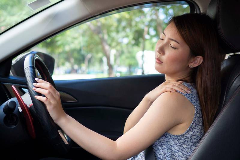 Young woman having pain her shoulder after driving. Getty Images
