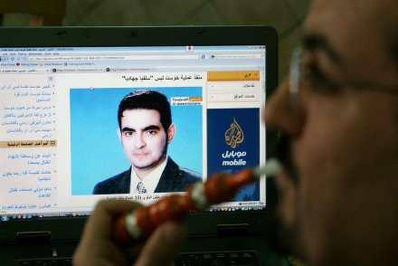 A Jordanian man smokes as he browses a  news website showing the suspected Jordanian suicide bomber Humam Khalil Abu-Mulal al-Balawi, at a coffe shop in Amman, Jordan, Thursday, Jan. 7, 2010. Al-Balawi, who is suspected of detonating the suicide bomb on  December 30, 2009, allegedly duped agents into granting him entry to the CIA base by leading them to think he would help track down al-Qaida's No. 2 leader, Ayman al-Zawahri, officials have said.(AP Photo/Nader Daoud) *** Local Caption ***  AMM103__Jordan_CIA_Afghan_Attack.jpg