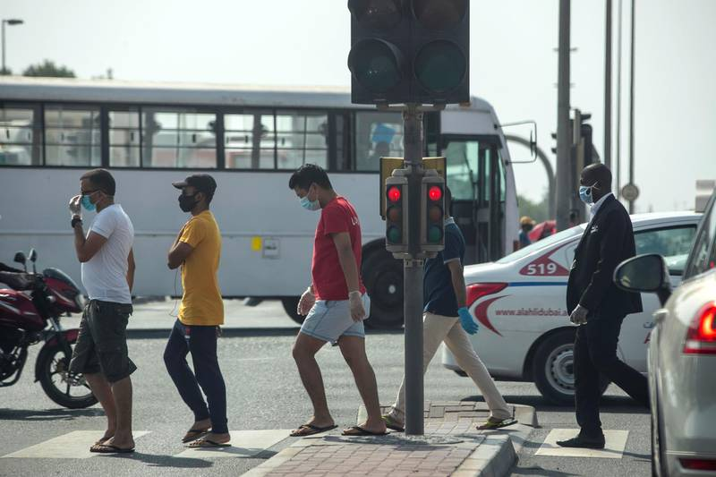 DUBAI, UNITED ARAB EMIRATES. 24 JUNE 2020. Standalone. Men cross a pedestrian crossing at a busy signal in the Al Quoz Inustrial area while wearing masks. With the end of the national sterilisation program curfews have been lifted but masks and social distancing is still in place. (Photo: Antonie Robertson/The National) Journalist: None. Section: National.