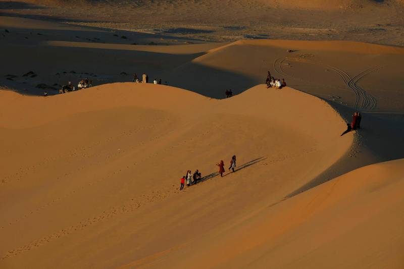 Residents walk on sand dunes in the Libyan desert oasis town of Ghadames April 19, 2013. Ghadames, a small town of around 11,000 people that lies on Libya's western border with Algeria, was a key destination for tourists who came to Libya before its Arab Spring uprising. But since the 2011 war that ousted Muammar Gaddafi, the flow of foreign holiday makers has ground to halt, as precarious security still taints Libya's image abroad. Picture taken April 19, 2013.   REUTERS/Ismail Zitouny (LIBYA - Tags: POLITICS CIVIL UNREST TRAVEL SOCIETY)