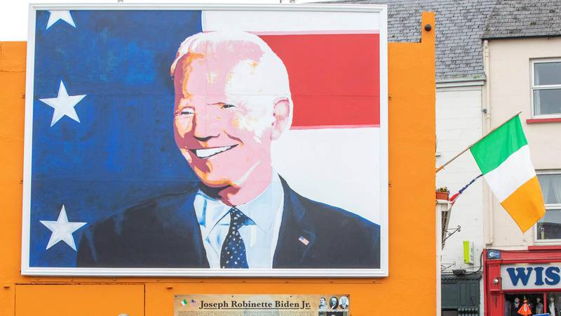 """Pedestrians read an information board beneath a giant painting of US Presidential candidate Joe Biden, erected in his ancestral home of Ballina, north west Ireland, on October 7, 2020. - Thousands of miles east of the White House in Ireland, a pop-art portrait of US presidential candidate Joe Biden towers over his ancestral hometown of Ballina, County Mayo. In the town on Ireland's rugged Atlantic coast, the Democrat's distant relatives are thrilled to have one of their own bidding for America's highest office. """"Obviously we're 100 percent behind Joe Biden,"""" Laurita Blewitt, the former vice-president's third cousin, told AFP. (Photo by PAUL FAITH / AFP)"""
