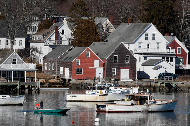 A boater motors past lobster boats moored off North Haven, Maine, Monday, March 16, 2020. The North Haven Select Board voted to ban visitors and seasonal residents immediately to prevent the spread of the coronavirus to the island in Penobscot Bay. For most people, the new coronavirus causes only mild or moderate symptoms, such as fever and cough. For some, especially older adults and people with existing health problems, it can cause more severe illness, including pneumonia. The vast majority of people recover from the new virus. (AP Photo/Robert F. Bukaty)