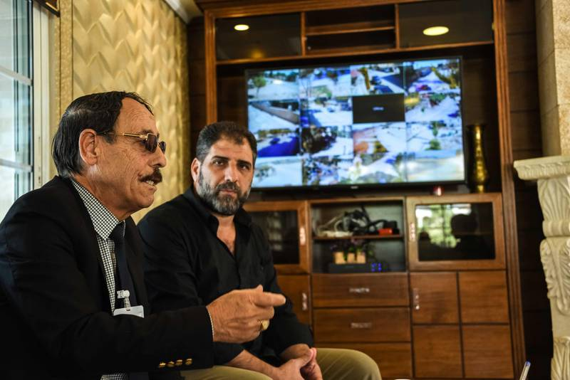 Baalbek, Lebanon, 10 October 2020. Abu Hassan Jaafar, head of one of a branch of the Jaafar family chats at his home in front of a screen filled with CCTV footage of the premesis perimeter. Elizabeth Fitt for The National