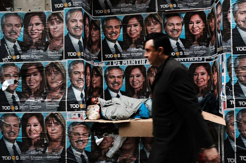 BUENOS AIRES, ARGENTINA - OCTOBER 28: A homeless man sleeps under posters of newly elected president Alberto Fernandez and his running mate Cristina Fernández de Kirchner as people walk through a central business district  the morning after populist was declared the winner in the presidential elections on October 28, 2019 in Buenos Aires, Argentina. The Populist-leaning Fernandez beat out business-friendly incumbent Mauricio Macri in the election that could will have huge consequences for the South American country. With a sharp drop in the peso, high unemployment and rising inflation, Argentines are looking for a leader to steer the economy towards stabilization. (Photo by Spencer Platt/Getty Images)