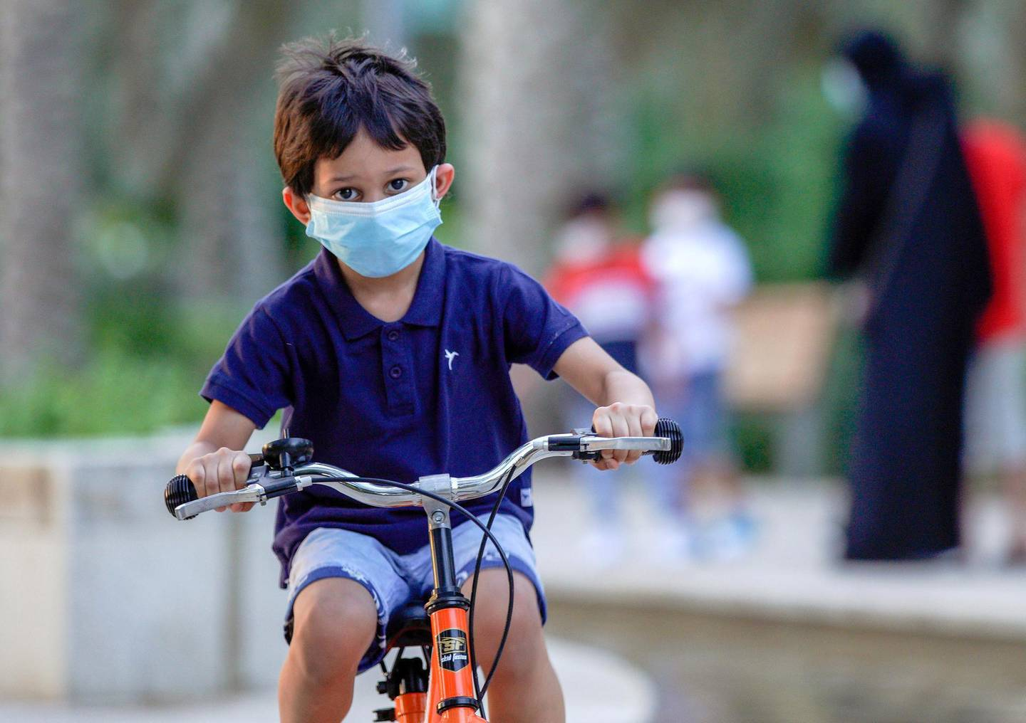 """Abu Dhabi, United Arab Emirates, October 26, 2020.  The """"new norm"""" of Covid-19 precautionary measures at Umm Al Emarat Park, Abu Dhabi, on a Monday afternoon.  It is a common sight to see children wearing face masks riding their bikes or scooters at the park.Victor Besa/The NationalSection:  NAReporter:"""